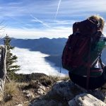 hiker above foggy bohinj valley